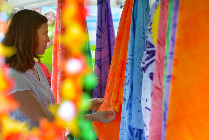 Young woman looking at sarongs for sale at the markets in Rarotonga Cook Islands